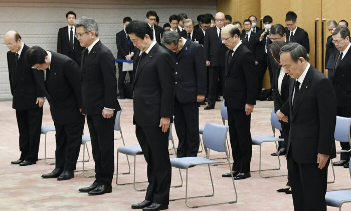 Japanese Prime Minister Shinzo Abe, center, observes a moment of silence at 2:46 p.m. when a magnitude 9.0 earthquake struck off Japan's northeastern coast nine years ago, at the prime minister's office in Tokyo on Wednesday, March 11, 2020. (Yoshitaka Sugawara/Kyodo News via AP)
