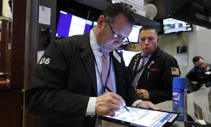 Traders Edward Curran (L) and Jonathan Mueller work on the floor of the New York Stock Exchange, N.Y., on March 12, 2020. (Richard Drew/AP Photo)