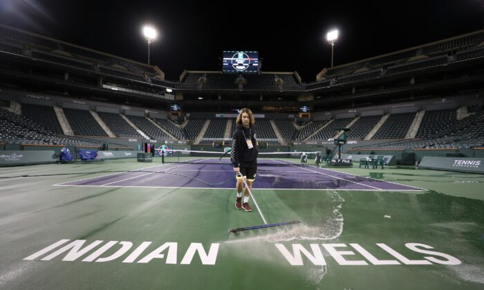 Courtmaster Jeffrey Brooker cleans the center court at the Indian Wells Tennis Garden in Indian Wells, California, on March 8, 2020. The BNP Paribas Open was cancelled as county officials declared a public health emergency when a case of coronavirus was confirmed in the area. (Al Bello/Getty Images)