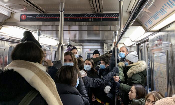 People wearing protective masks ride a train in New York on Feb. 29, 2020. (Chung I Ho/The Epoch Times)