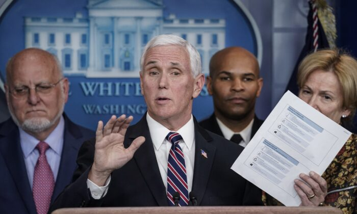 Vice President Mike Pence holds up a copy of community health guidelines during a press briefing with members of the White House Coronavirus Task Force at the White House in Washington on March 9, 2020. (Drew Angerer/Getty Images)