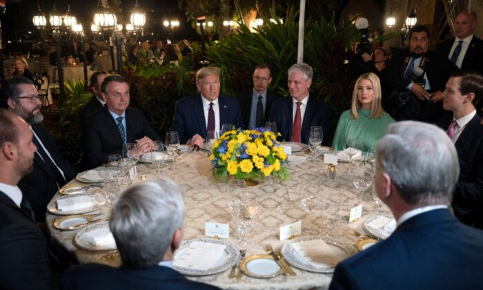 President Donald Trump, center, speaks with Brazilian President Jair Bolsonaro, left, during a dinner at Mar-a-Lago in Palm Beach, Florida, on March 7, 2020. (Jim Watson/AFP via Getty Images)