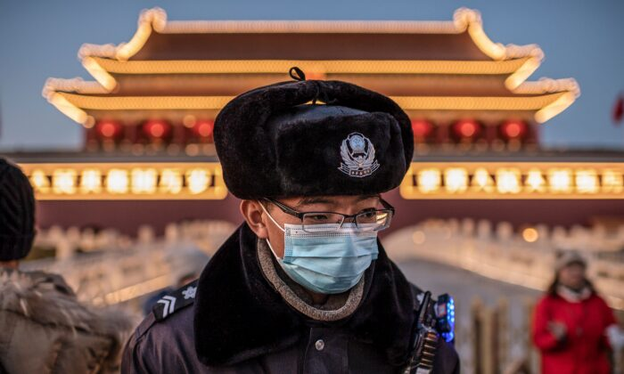 A police officer wearing a protective mask walks past the portrait of late communist leader Mao Zedong (not pictured) at Tiananmen Gate in Beijing on Jan. 23, 2020. (NICOLAS ASFOURI/AFP via Getty Images)