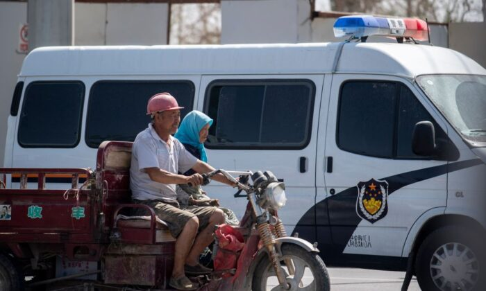 Local Muslims pass a police car in their vehicle in Hotan in China's Xinjiang Uighur Autonomous Region on June 23, 2017. (Johannes Eisele/AFP via Getty Images)