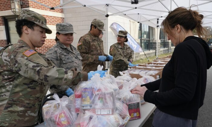 National Guard troops give food to residents of New Rochelle, New York, at New Rochelle High School March 12, 2020. The National Guard is helping to clean surfaces and deliver food in the one-mile radius containment area around a point near a synagogue connected to some existing cases of what appears to be the nation's biggest cluster of cases of COVID-19. (TIMOTHY A. CLARY/AFP via Getty Images)