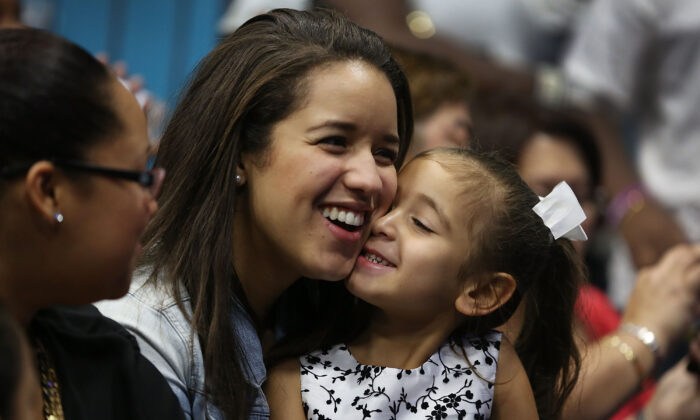 Nathalie Ogando sits with her adopted cousin, Lean Martinez, 5, after she was adopted during a ceremony in an adoption court on National Adoption Day marked at the Miami Children's Museum in Miami, Fla., on Nov. 20, 2015. (Joe Raedle/Getty Images)