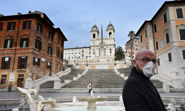 A man wearing a protective mask walks by a deserted Piazza di Spagna in central Rome, Italy, on March 12, 2020. (Alberto Pizzoli/AFP via Getty Images)