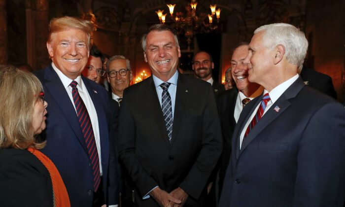 Brazil's presidential press office, Brazil's President Jair Bolsonaro, center, stands with President Donald Trump, second from left, Vice President Mike Pence, right, and Brazil's Communications Director Fabio Wajngarten, behind Trump partially covered, during a dinner in Florida on March 7, 2020. (Alan Santos/Brazil's Presidential Press Office via AP)