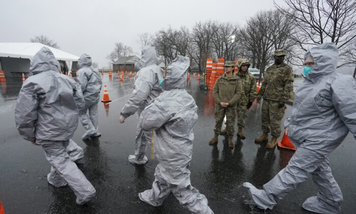 Workers in protective suits get ready while waiting for people to be tested as they arrive by car at the state's first drive through COVID-19 Mobile Testing Center at Glen Island Park in New Rochelle, New York, on March 13, 2020. (Timothy A. Clary/AFP via Getty Images)