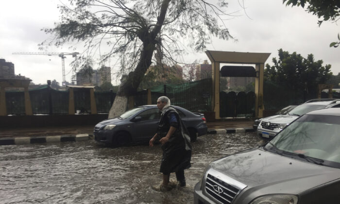 A man wears makeshift rain gear as he navigates a flooded road after heavy rains in the Zamalek district of Cairo, Egypt, on March 12, 2020. (Maya Alleruzzo/AP Photo)