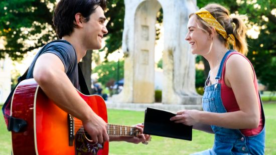man with red guitar talking to girl with diary
