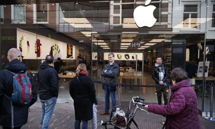 People stand outside an Apple store in Haarlem in the Netherlands on March 14, 2020. (Olaf Kraak/AFP via Getty Images)