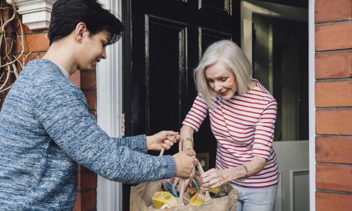 A young man delivers groceries to a woman at her home in a file photo. (DGLimages/Shutterstock)