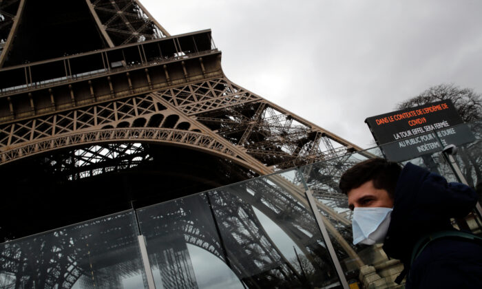 A man wearing a mask walks pasts the Eiffel tower closed after the French government banned all gatherings of over 100 people to limit the spread of the virus COVID-19, in Paris, on March 14, 2020. (AP Photo/Christophe Ena)