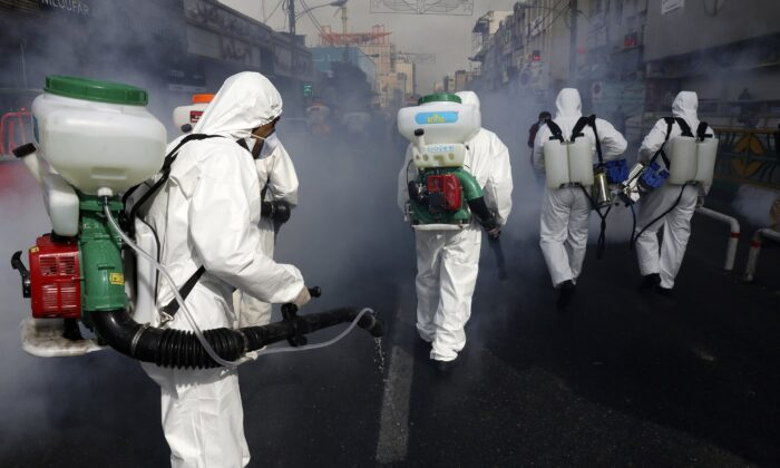 Firefighters disinfect a street against the CCP virus in western Tehran, Iran, on March 13, 2020. (Vahid Salemi/AP Photo)