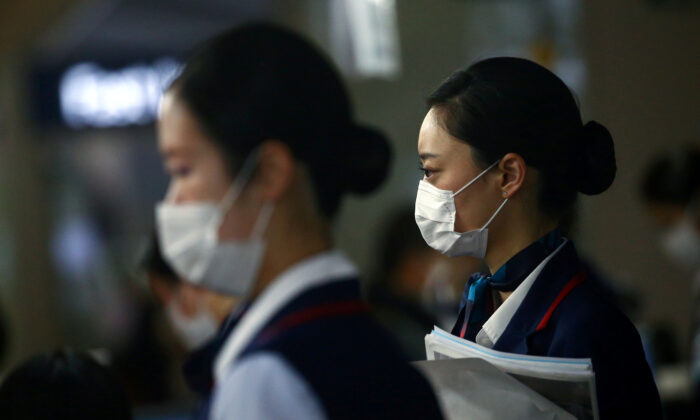 Employes wearing protective masks following the outbreak of the coronavirus disease (COVID-19) are pictured at the Kansai International Airport in Osaka, Japan, on March 14, 2020. (Edgard Garrido/Reuters)