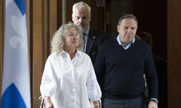 Quebec Premier Francois Legault and Quebec Minister Responsible for Seniors and Informal Caregivers Marguerite Blais walk to a daily news conference at the legislature in Quebec City on March 14, 2020. (The Canadian Press/Jacques Boissinot)