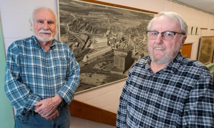 Francesco Spertini (L) and Mario Leblanc are seen in front of a historical picture of the open pit mine in Asbestos, Que., on March 11, 2020. (Paul Chiasson/The Canadian Press)