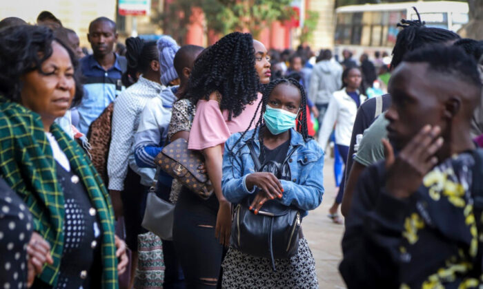 A Kenyan woman wears a surgical face mask on a busy street in downtown Nairobi, Kenya, on March 13, 2020. (Patrick Ngugi/AP Photo)
