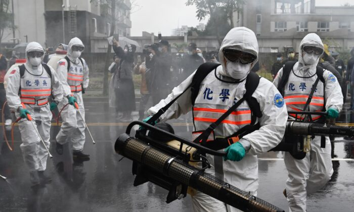 Soldiers from military chemical units take part in a drill organized by the New Taipei City government to prevent the spread of the COVID-19 coronavirus, in the Xindian District of New Taipei, Taiwan, on March 14, 2020. (Sam Yeh/AFP via Getty Images)