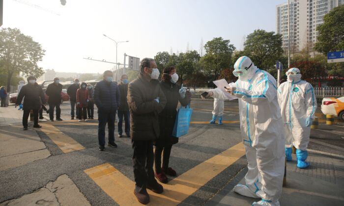 Medical workers dressed in protective suits check patients who recovered from COVID-19 as they arrive to be tested again at a hospital in Wuhan on March 14, 2020. (STR/AFP via Getty Images)