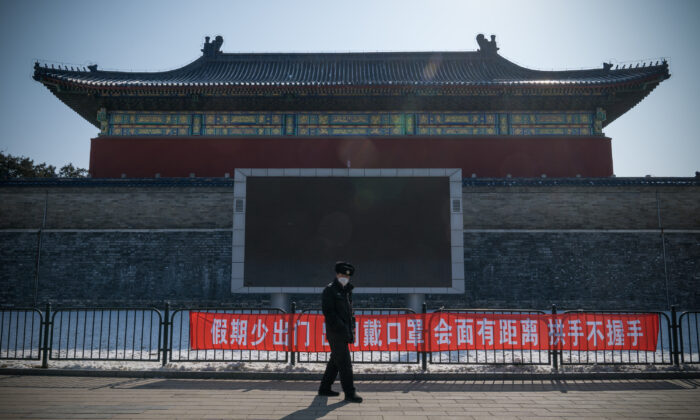 "A security guard walks past a propaganda banner saying, ""Do Not Leave Home Often During Holidays, Wear a Mask When Going Out, Keep a Distance and Do Not Shake Hands When Meeting"" in Temple of Heaven Park, Beijing on Feb. 15, 2020. (Andrea Verdelli/Getty Images)"