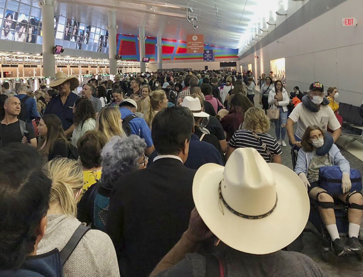 People wait in line to go through the customs at airport