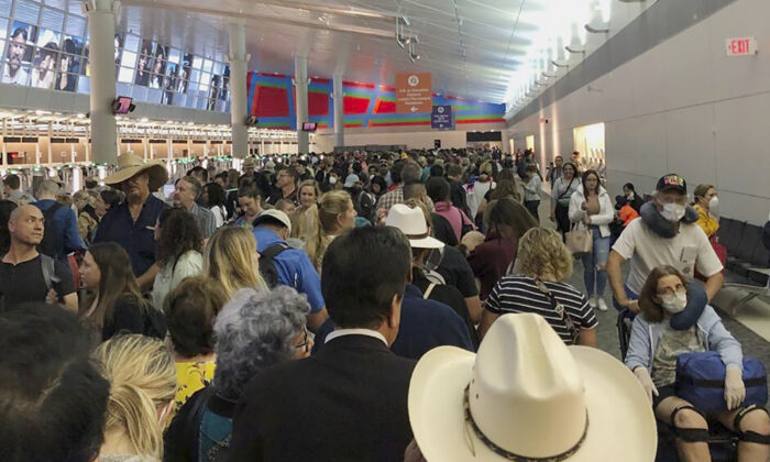 People wait in line to go through customs at Dallas Fort Worth International Airport in Grapevine, Texas, on March 14, 2020. (Austin Boschen via AP)