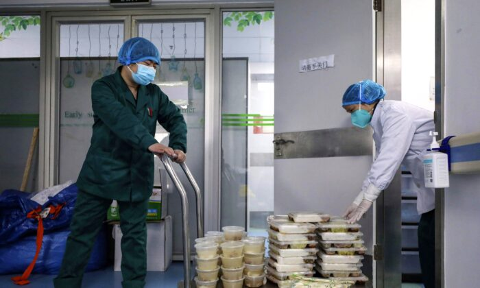 Workers deliver meals to Jinyintan Hospital, designated for critical COVID-19 patients, in Wuhan, China, on Feb. 13, 2020. (Chinatopix Via AP)