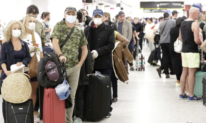 Travellers wait in line at the Miami International Airport in Miami on March 13, 2020. (AP Photo/Wilfredo Lee)