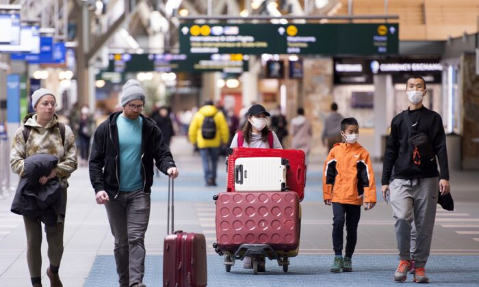 Travellers are seen at Vancouver International Airport in Richmond, B.C., on March 13, 2020. (The Canadian Press/Jonathan Hayward)
