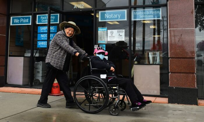 An elderly woman wears a face mask as a precaution against COVID-19, coronavirus, while being pushed in her wheelchair in Monterey Park, Calif., on March 10, 2020. (Frederic J. Brown/AFP via Getty Images)