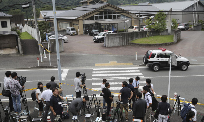 Journalists gather in front of Tsukui Yamayuri-en, a facility for the handicapped where a former care home employee killed 19 disabled people, in Sagamihara, outside Tokyo, Japan, on July 26, 2016. (Eugene Hoshiko/File/AP Photo)