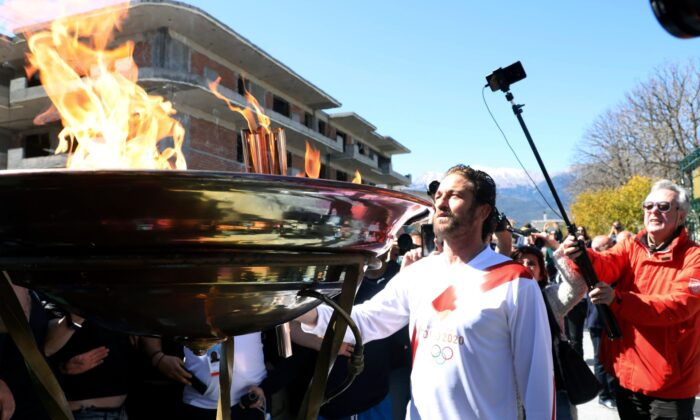 US actor Gerard Butler lights an altar as a torchbearer during the Olympic torch relay of the 2020 Tokyo Olympic Games in the southern Greek town of Sparta on March 13, 2020. (AP Photo)