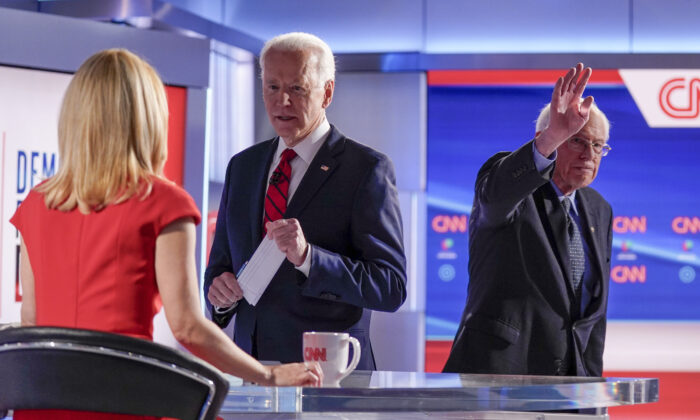 Former Vice President Joe Biden, center, stops to talk with CNN anchor Dana Bash, left, as Sen. Bernie Sanders (I-Vt.) right, waves after they participated in a Democratic presidential primary debate at CNN Studios in Washington on March 15, 2020. (Evan Vucci/AP Photo)