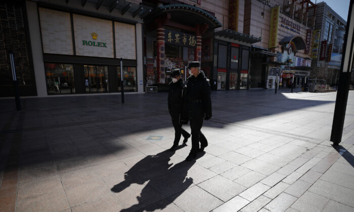 Security guards patrol the quiet Wangfujing shopping, a usually popular tourist spot before the new coronavirus outbreak in Beijing, on March 10, 2020. China's consumer spending and other business activity fell even more than expected in January and February due to its virus outbreak, adding to the ruling Communist Party's challenges as it tries to revive the world's second-largest economy. (Andy Wong/AP)