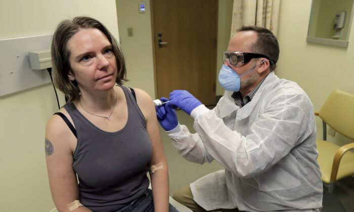 A pharmacist gives Jennifer Haller the first shot in the first-stage safety study clinical trial of a potential vaccine for COVID-19 at the Kaiser Permanente Washington Health Research Institute in Seattle on March 16, 2020. The vaccine was developed by Moderna. (Ted S. Warren/AP Photo)