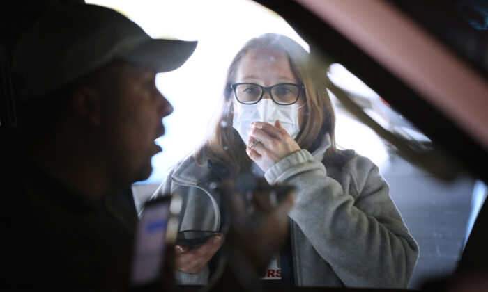 Carroll Hospital Critical Care Unit Clinical Manager Stephanie Bakert talks to a person through his car window using a mobile phone before testing him for the coronavirus at a drive-thru station in the hospital's parking garage in Westminster, Maryland on March 16, 2020. (Chip Somodevilla/Getty Images)