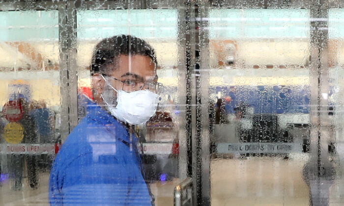 A worker at Baltimore/Washington International Thurgood Marshall Airport wears a mask as he cleans a glass door in Baltimore, Maryland on March 13, 2020. (Mark Wilson/Getty Images)