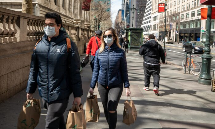 People carry groceries while wearing masks and gloves in New York City on March 14, 2020. (Apu Gomes/AFP via Getty Images)