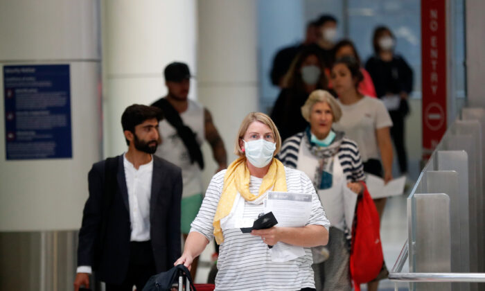 SYDNEY, AUSTRALIA - MARCH 16: Passengers arrives at Sydney airport on March 16, 2020 in Sydney, Australia. Strict new border measures to contain the spread of COVID-19 have come into effect Monday, requiring all overseas arrivals to Australia to self-isolate for 14 days. Australia currently has 300 confirmed cases of coronavirus while five people have died – four in NSW and one in Queensland. (Photo by Brendon Thorne/Getty Images)