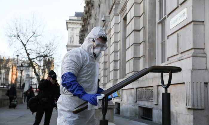A man in a protective suit cleans a hand rail as the number of coronavirus cases (COVID-19) grows around the world, in London, Britain, on March 16, 2020. (Simon Dawson/Reuters)