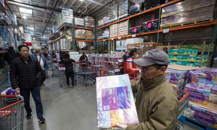 A man carries a multi-package of facial tissues while shopping along with hundreds of others who filled a Costco store in Burnaby, B.C., on the morning of March 16, 2020, amid concerns about the spread of the novel coronavirus. (The Canadian Press/Darryl Dyck)