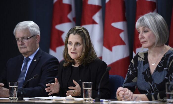 (L-R) Transport Minister Marc Garneau, Deputy Prime Minister Chrystia Freeland, and Health Minister Patty Hajdu participate in a press conference on COVID-19 at the National Press Theatre in Ottawa March 16, 2020. (The Canadian Press/Justin Tang)