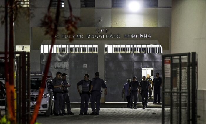 Military police officers are seen at the main entrance of the Doctor Edgar Magalhaes Noronha (Pemano) Penitentiary during a riot in Tremembe, 155 km from Sao Paulo, Brazil, early on March 17, 2020. (Photo by Lucas Lacaz/AFP via Getty Images)