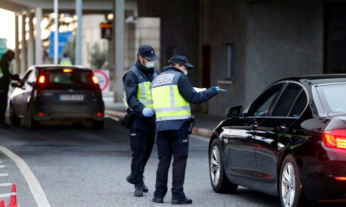 Spanish police officers check a car at the border between Portugal and Spain, following an order from the Spanish government to set up controls at its land borders over coronavirus, in Vilar Formoso, Portugal, on March 17, 2020. (Rafael Marchante/Reuters)