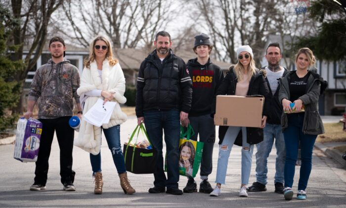 Jordan Banman, left to right, Jennifer Teufel-Shatilla, Mason Shatilla, Dave Shatilla, Zack St. Pierre, Sarah Moreby and Tori Teufel pose for a photo in their Burlington, Ont. neighbourhood on March 16, 2020. (Peter Power/The Canadian Press)