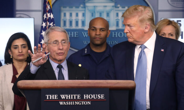 President Donald Trump listens as Director of the National Institute of Allergy and Infectious Diseases Anthony Fauci, a member of the White House coronavirus task force, answers a question about the virus and the current U.S. outbreak during a news briefing at the White House on March 16, 2020. (Leah Millis/Reuters)