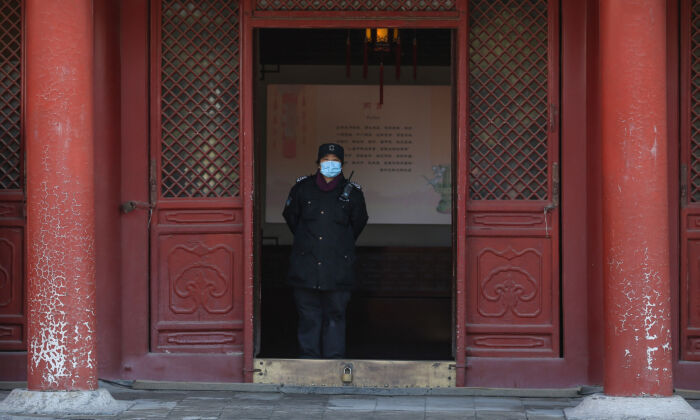 A security guard wearing a face mask at the Imperial Palace as it reopens to the public in Shenyang, China, on March 17, 2020. (STR/AFP via Getty Images)
