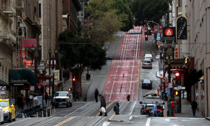 Few pedestrians walk along Powell Street during commute hours on March 16, 2020 in San Francisco, California. Public areas around the country are mostly empty as people around the country are staying away from from large gatherings in an attempt to slow the spread of COVID-19. (Justin Sullivan/Getty Images)
